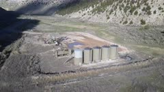 Aerial oil wells pumping mountain valley Utah. Oil rig, pumps and storage structure with industrial facilities to drill wells, extract and process crude oil and natural gas. Store product until it can be transported to refining and marketing. Accidents and pollution spills damage environment. Mountain valley Utah. 4K footage video.  Despain Rekindle Photo. 924