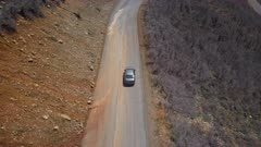 Aerial car on mountain road followed by drone. Follow tracking car while exploring wilderness scenic mountain road environment. Landscape central Utah. Early spring with new growth in forest. Nature and environment. Beautiful natural view. Drone flight above vehicle. 4K HD video footage. Despain Rekindle Photo. 941