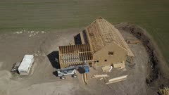Aerial carpenters working new rural house construction. Aerial rural farm house green agricultural field valley. Carpenters work to build new construction. Wood lumber frame. Spring weather mountain valley green agriculture field. Seasonal rural farm community. Homes, barns and buildings. Drone flight. 4K HD video footage. Despain Rekindle Photo. 990