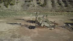 Aerial industrial oil well pump mountain valley Utah. Oil rig, pumps and storage structure with industrial facilities to drill wells, extract and process crude oil and natural gas. Store product until it can be transported to refining and marketing. Accidents and pollution spills damage environment. Mountain valley Utah. 4K footage video.  Despain Rekindle Photo. 913