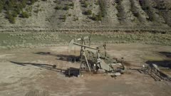 Aerial pair of industrial oil well pumps mountain valley. Oil rig, pumps and storage structure with industrial facilities to drill wells, extract and process crude oil and natural gas. Store product until it can be transported to refining and marketing. Accidents and pollution spills damage environment. Mountain valley Utah. 4K footage video.  Despain Rekindle Photo. 912