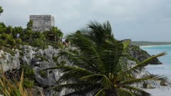 Tulum temple above ocean beach tropical Mexico HD. Pre Columbian Mayan ancient walled city along coast. Built on cliff over looking beach and Caribbean Ocean east shore of Yucatan Peninsula. Today a popular site for tourists. El Castillo, the Temple of the Frescoes, and the Temple of the Descending God are the three most famous buildings. HD video footage. Despain Rekindle Photo. 546