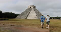 Chichen Itza couple walk to El Castillo pyramid. Pre Columbian city built by the Maya people in Yucatan, Mexico. One of the largest Maya cities. Most visited archaeological sites in Mexico. Developed around 600 AD. Castillo pyramid or Temple of Kukulcan, Temple of Warriors and the Great Ball Court, Sacred Cenote, and observatory are main buildings. DCI 4K HD video footage. Despain Rekindle Photo. 215