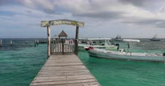 Morelos Port marina pier yacht club ocean. Town, marina and seaport in Quintana Roo, Mexico. near Cancun. Beach, resorts and restaurants along Caribbean Ocean shore. Tourist and tourism destination in tropical environment. Beautiful blue water and pier to yacht club and boat anchors. DCI 4K video footage. Despain Rekindle Photo. 188