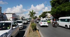 Mexico Play del Carmen busy road traffic. Tourist destination for Luxury resorts along Mexican Mayan Riviera near Cancun. Local business and residents along road intersection. Busy street, Mexican culture and lifestyle. Urban city center. Caribbean ocean vacation. Family, honeymoon and couple travel trip. Driving car, trucks, bus and motorcycle. DCI 4K HD video footage. Despain Rekindle Photo. 532