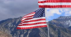 United States of America flags mountain narrow focus. The flag of the United States of America, often referred to as the American flag, is the national flag of the United States of America. Nation's most widely recognized symbols and powerful symbol. Beautiful Wasatch Mountains and valley in background. 4K HD video footage. Despain Rekindle Photo. 631