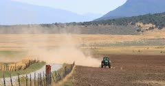 Desert drought farm tractor disking dusty dirt. Dry drought dusty seasonal environment. Rural community where farming is the main source of employment and income. Farmer in tractor preparing field for planting or drilling alfalfa and grain seeds. Agriculture supplies food and livestock with nourishment. 4K video footage. Despain Rekindle Photo. 341