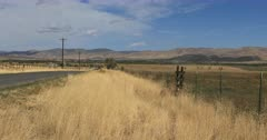 Rural country road fence line mountain. Farmland with fences along public road. Posted for private hunting club. Wooden ladder over barb wire fence. Dry grass in autumn or fall during long term drought. High mountain valley desert. Outdoor sport and recreation involving wildlife management and harvest. HD video footage. Despain Rekindle Photo.  378