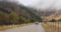 Rural mountain road truck away autumn colors storm. Pickup. Beautiful autumn fall colors along Wasatch Mountains. Rural farming community dirt road through hills to canyon. Pickup truck drives on gravel road. Aspen, maple and oak trees colorful leaves change as winter starts to set in. Low clouds drift past view as snow is falling higher elevation. DCI 4K HD video footage. Despain Rekindle Photo. 429