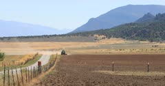 Tractor farm dusty desert field drought. Dry drought dusty seasonal environment. Rural community where farming is the main source of employment and income. Farmer in tractor preparing field for planting or drilling alfalfa and grain seeds. Agriculture supplies food and livestock with nourishment. 4K video footage. Despain Rekindle Photo. 340