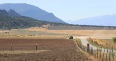 Tractor farm dusty mountain desert field drought. Dry drought dusty seasonal environment. Rural community where farming is the main source of employment and income. Farmer in tractor preparing field for planting or drilling alfalfa and grain seeds. Agriculture supplies food and livestock with nourishment. 4K video footage. Despain Rekindle Photo. 340