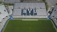 Aerial BYU University empty football stadium climb. Brigham Young University in Provo, Utah. Private church research owned by The CHurch of Jesus Christ of Latter-day Saints, LDS or Mormon religion. Largest religious school in the USA with 30,000 students. Sports teams are known as Cougars. Independent in NCAA Division I. Honor Code maintains a high moral standard with students and employees. No alcohol, tobacco or pre marital sex is allowed. 4K HD video footage. Despain Rekindle Photo. 031