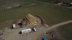 Aerial circle new home construction rural farm house. Aerial rural farm house green agricultural field valley. Carpenters work to build new construction. Wood lumber frame. Spring weather mountain valley green agriculture field. Seasonal rural farm community. Homes, barns and buildings. Drone flight. 4K HD video footage. Despain Rekindle Photo. 986