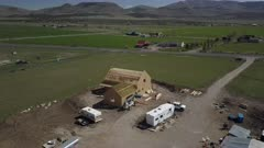 Aerial drone fly rural farm house construction. Aerial rural farm house green agricultural field valley. Carpenters work to build new construction. Wood lumber frame. Spring weather mountain valley green agriculture field. Seasonal rural farm community. Homes, barns and buildings. Drone flight. 4K HD video footage. Despain Rekindle Photo. 989