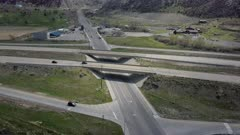 Aerial flight overhead interstate freeway highway traffic. Rural community along travelled road. Turn off to mountain canyon and valley. Car and trucks driving, commuting for business and pleasure. Use of gas leads to pollution and possible global warming and climate change.