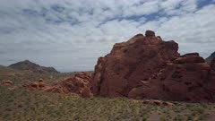 Aerial fly to red rock desert near Valley of Fire Nevada. Near Valley of Fire State Park is a public recreation and nature preservation area Nevada. Scenic desert landscape mountains. By shore of Lake Mead recreation area outside of Las Vegas. Natural ecological tourist tourism destination for hiking. Easy access by car or motorhome RV. Hot arid red and multicolored rock formation wilderness. 4K HD video footage. Despain Rekindle Photo. 093
