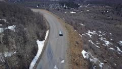 Aerial follow car on mountain road spring snow. Follow tracking car while exploring wilderness scenic mountain road environment. Landscape central Utah. Early spring with new growth in forest. Nature and environment. Beautiful natural view. Drone flight above vehicle. 4K HD video footage. Despain Rekindle Photo. 940