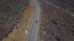 Aerial following car on mountain road by drone. Follow tracking car while exploring wilderness scenic mountain road environment. Landscape central Utah. Early spring with new growth in forest. Nature and environment. Beautiful natural view. Drone flight above vehicle. 4K HD video footage. Despain Rekindle Photo. 941
