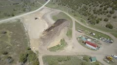 Aerial gravel pit industrial construction site mountain valley. Drone flight over rural hills and mountains. Industrial complex with earth moving and heavy equipment. Road and building construction. Dirt roads. 4K HD video footage. Despain Rekindle Photo. 010