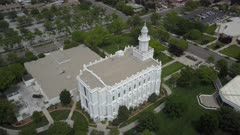 Aerial LDS St George Utah Temple white building park. Flight over sacred Temple, Church of Jesus Christ of Latter-day Saints, Mormon or LDS. Built late 1800's. Pioneer white stone structure. Called House of the Lord. City town center of once a rural community in southwest Utah. Eternal religious ceremony. Religion belief of eternal life with God and Jesus Christ. Spring season. 4K video footage. Despain Rekindle Photo. 059