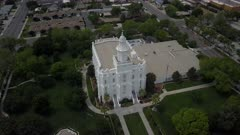 Aerial LDS St George Utah Temple white building park part 3. Flight over sacred Temple, Church of Jesus Christ of Latter-day Saints, Mormon or LDS. Built late 1800's. Pioneer white stone structure. Called House of the Lord. City town center of once a rural community in southwest Utah. Eternal religious ceremony. Religion belief of eternal life with God and Jesus Christ. Spring season. 4K video footage. Despain Rekindle Photo. 059