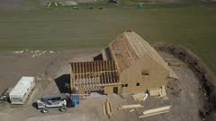 Aerial new home construction carpenters working. Aerial rural farm house green agricultural field valley. Carpenters work to build new construction. Wood lumber frame. Spring weather mountain valley green agriculture field. Seasonal rural farm community. Homes, barns and buildings. Drone flight. 4K HD video footage. Despain Rekindle Photo. 992