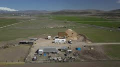 Aerial new home construction rural farm fly to. Aerial rural farm house green agricultural field valley. Carpenters work to build new construction. Wood lumber frame. Spring weather mountain valley green agriculture field. Seasonal rural farm community. Homes, barns and buildings. Drone flight. 4K HD video footage. Despain Rekindle Photo. 994