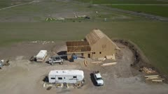 Aerial new home construction rural farm pull back. Aerial rural farm house green agricultural field valley. Carpenters work to build new construction. Wood lumber frame. Spring weather mountain valley green agriculture field. Seasonal rural farm community. Homes, barns and buildings. Drone flight. 4K HD video footage. Despain Rekindle Photo. 994