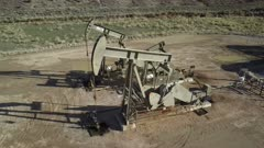 Aerial oil wells pumping high mountain valley Utah. Oil rig, pumps and storage structure with industrial facilities to drill wells, extract and process crude oil and natural gas. Store product until it can be transported to refining and marketing. Accidents and pollution spills damage environment. Mountain valley Utah. 4K footage video.  Despain Rekindle Photo. 918