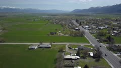 Aerial rural city Main Street homes and traffic green spring part 2. Spring seasonal weather. Green grass, fields and tree growing in warm temperature. House, home, barns and shed along streets and roads. Small farming community town in mountain valley. Cityscape and agriculture and farming based economy. 4K HD video footage. Despain Rekindle Photo. 013