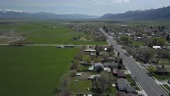 Aerial rural city Main Street homes and traffic green spring pull back. Spring seasonal weather. Green grass, fields and tree growing in warm temperature. House, home, barns and shed along streets and roads. Small farming community town in mountain valley. Cityscape and agriculture and farming based economy. 4K HD video footage. Despain Rekindle Photo. 013
