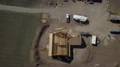 Aerial rural farm home under construction climbing overhead. Aerial rural farm house green agricultural field valley. Carpenters work to build new construction. Wood lumber frame. Spring weather mountain valley green agriculture field. Seasonal rural farm community. Homes, barns and buildings. Drone flight. 4K HD video footage. Despain Rekindle Photo. 982