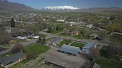Aerial rural farm town community homes barn snow mountain. Spring seasonal weather. Green grass, fields and tree growing in warm temperature. House, home, barns and shed along streets and roads. Small farming community town in mountain valley. Cityscape and agriculture and farming based economy. 4K HD video footage. Despain Rekindle Photo. 973