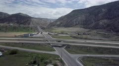 Aerial flight overhead interstate freeway highway traffic. Rural community along traveled road. Turn off to mountain canyon and valley. Car and trucks driving, commuting for business and pleasure. Use of gas leads to pollution and possible global warming and climate change.