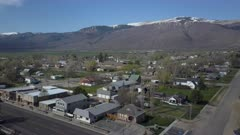Aerial rural town business homes and church snowy mountain. Spring seasonal weather. Green grass, fields and tree growing in warm temperature. House, home, barns and shed along streets and roads. Small farming community town in mountain valley. Cityscape and agriculture and farming based economy. 4K HD video footage. Despain Rekindle Photo. 966