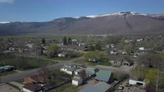Aerial rural town business homes towards church snowy mountain. Spring seasonal weather. Green grass, fields and tree growing in warm temperature. House, home, barns and shed along streets and roads. Small farming community town in mountain valley. Cityscape and agriculture and farming based economy. 4K HD video footage. Despain Rekindle Photo. 966
