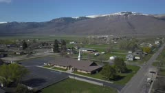 Aerial rural town business homes towards church snowy mountain pull. Spring seasonal weather. Green grass, fields and tree growing in warm temperature. House, home, barns and shed along streets and roads. Small farming community town in mountain valley. Cityscape and agriculture and farming based economy. 4K HD video footage. Despain Rekindle Photo. 966