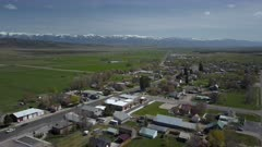 Aerial rural town center Main Street traffic homes green spring. Spring seasonal weather. Green grass, fields and tree growing in warm temperature. House, home, barns and shed along streets and roads. Small farming community town in mountain valley. Cityscape and agriculture and farming based economy. 4K HD video footage. Despain Rekindle Photo. 015