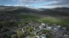 Aerial rural town city center to ranch house. Spring seasonal weather. Green grass, fields and tree growing in warm temperature. House, home, barns and shed along streets and roads. Small farming community town in mountain valley. Cityscape and agriculture and farming based economy. 4K HD video footage. Despain Rekindle Photo. 054