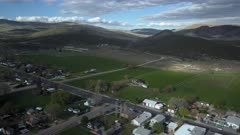 Aerial rural town city center to ranch house pull back. Spring seasonal weather. Green grass, fields and tree growing in warm temperature. House, home, barns and shed along streets and roads. Small farming community town in mountain valley. Cityscape and agriculture and farming based economy. 4K HD video footage. Despain Rekindle Photo. 054