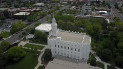 Aerial St George Utah LDS Temple circle side white building. Flight over sacred Temple, Church of Jesus Christ of Latter-day Saints, Mormon or LDS. Built late 1800's. Pioneer white stone structure. Called House of the Lord. City town center of once a rural community in southwest Utah. Eternal religious ceremony. Religion belief of eternal life with God and Jesus Christ. Spring season. 4K video footage. Despain Rekindle Photo. 058