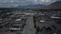 Aerial urban business street Provo Utah valley fast motion. Aerial overhead drone footage business road mountain valley. Home of Brigham Young University, BYU. Metropolitan city center cityscape. Traffic, stores and business building. Public transportation including UDOT bus and front runner train to Salt Lake city as well as Amtrak. Busy urban center. Mall and department stores. 4K HD video footage. Despain Rekindle Photo. 131