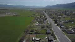 Aerial rural city Main Street homes and traffic green spring. Spring seasonal weather. Green grass, fields and tree growing in warm temperature. House, home, barns and shed along streets and roads. Small farming community town in mountain valley. Cityscape and agriculture and farming based economy. 4K HD video footage. Despain Rekindle Photo. 013