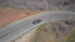 Aerial steep mountain road following car around curve by drone. Follow tracking car while exploring wilderness scenic mountain road environment. Landscape central Utah. Early spring with new growth in forest. Nature and environment. Beautiful natural view. Drone flight above vehicle. 4K HD video footage. Despain Rekindle Photo. 944