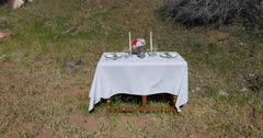 Fancy formal dinning room dinner table outdoors. Formal table setup in nature for a romantic date with spouse, husband or wife. Plates, white cloth, napkins, flowers, candles and wine glass. Near river and picnic camping area park. Love and friendship. Memory. 4K HD video footage. Despain Rekindle Photo. 5375