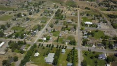 Aerial rural community Fountain Green central Utah. Aerial rural farming community agricultural economy. Spring summer weather mountain valley green agriculture field. Seasonal rural farm city. Homes, barns and buildings. Drone flight. 4K HD video footage. Despain Rekindle Photo. 014
