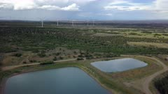 Aerial rural community ponds windmill turbines electricity. Wind farm in the town of Monticello, south eastern Utah. Important source of renewable energy by wind turbines. Scenic mountain in background. Three bladed and pointed into the wind by computer-controlled motors. Towers nearly 280 feet tall. Wind power is renewable energy for homes and business. DCI 4K HD video footage. Despain Rekindle Photo. 005