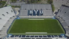 Aerial BYU University football stadium empty. Brigham Young University in Provo, Utah. Private church research owned by The Church of Jesus Christ of Latter-day Saints, LDS or Mormon religion. Largest religious school in USA. Sports teams are known as Cougars. Independent in NCAA Division I. Strict Honor Code maintains a high moral standard with students and employees. No alcohol, tobacco or pre marital sex is allowed. 4K HD video footage. Despain Rekindle Photo. 027