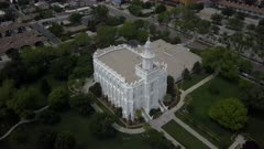 Aerial LDS St George Utah Temple white building park part 2. Flight over sacred Temple, Church of Jesus Christ of Latter-day Saints, Mormon or LDS. Built late 1800's. Pioneer white stone structure. Called House of the Lord. City town center of once a rural community in southwest Utah. Eternal religious ceremony. Religion belief of eternal life with God and Jesus Christ. Spring season. 4K video footage. Despain Rekindle Photo. 059