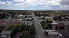 Aerial rural town Main street church park Monticello Utah. Business traffic center of city. Rural community southern Utah, San Juan County. High mountain plateau, dry farm landscape. Remote agriculture economy. Homes, fields and small town business. 4K HD video footage. Despain Rekindle Photo. 038